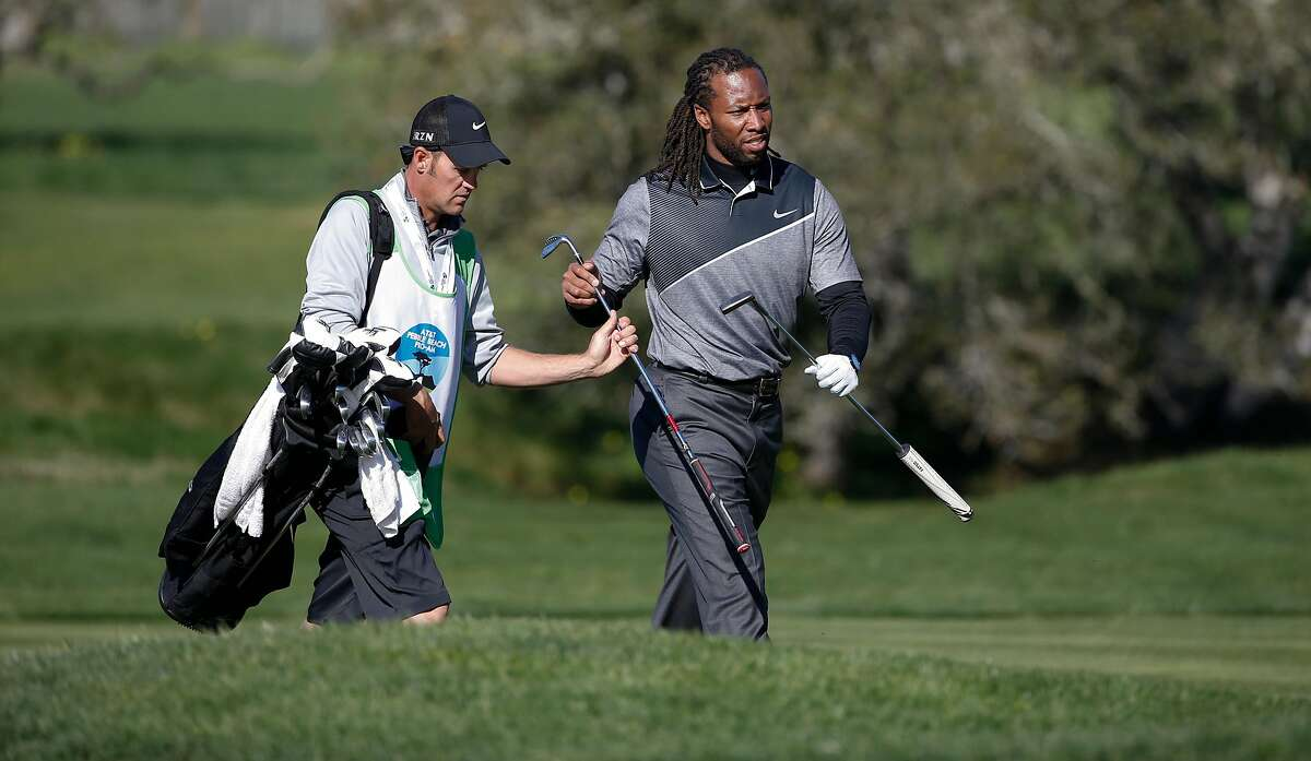 Larry Fitzgerald, a wide receiver for the Arizona Cardinals grabs his putter from his caddie as he plays the 2nd hole at the Pebble Beach Golf Links, during the third round of the AT&T Pebble Beach Pro-Am on Sat. February 13, 2016, in Pebble Beach, California.