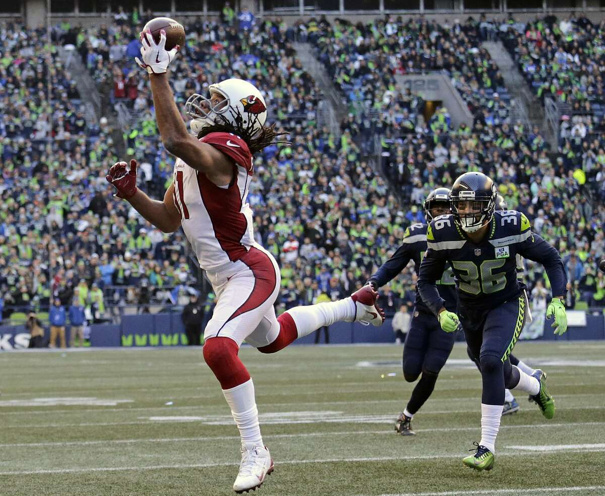 """FILE - In this Dec. 30, 2018, file photo, Arizona Cardinals' Larry Fitzgerald, left, snags a one-handed touchdown pass against the Seattle Seahawks during the first half of an NFL football game, in Seattle. Star receiver Larry Fitzgerald is returning to the Arizona Cardinals for a 16th NFL season. The Cardinals announced Wednesday, Jan. 23, 2019, that they signed the 35-year-old Fitzgerald to a one-year contract. Team president Michael Bidwell says, """"No player has meant more to this franchise or this community than Larry Fitzgerald.""""(AP Photo/John Froschauer, File)"""