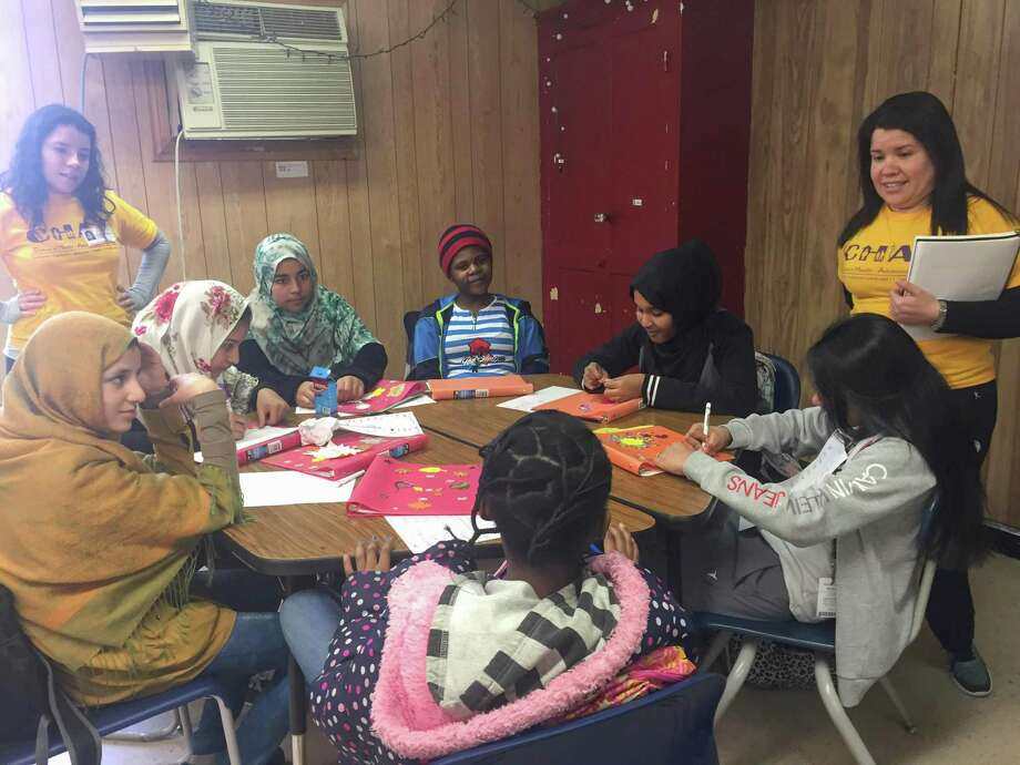Members of CHAT's Girls Club for Success learn about health with the help of facilitators Daniela Garcia (left) and Rosbel Brito. Photo: Rebecca Hazen