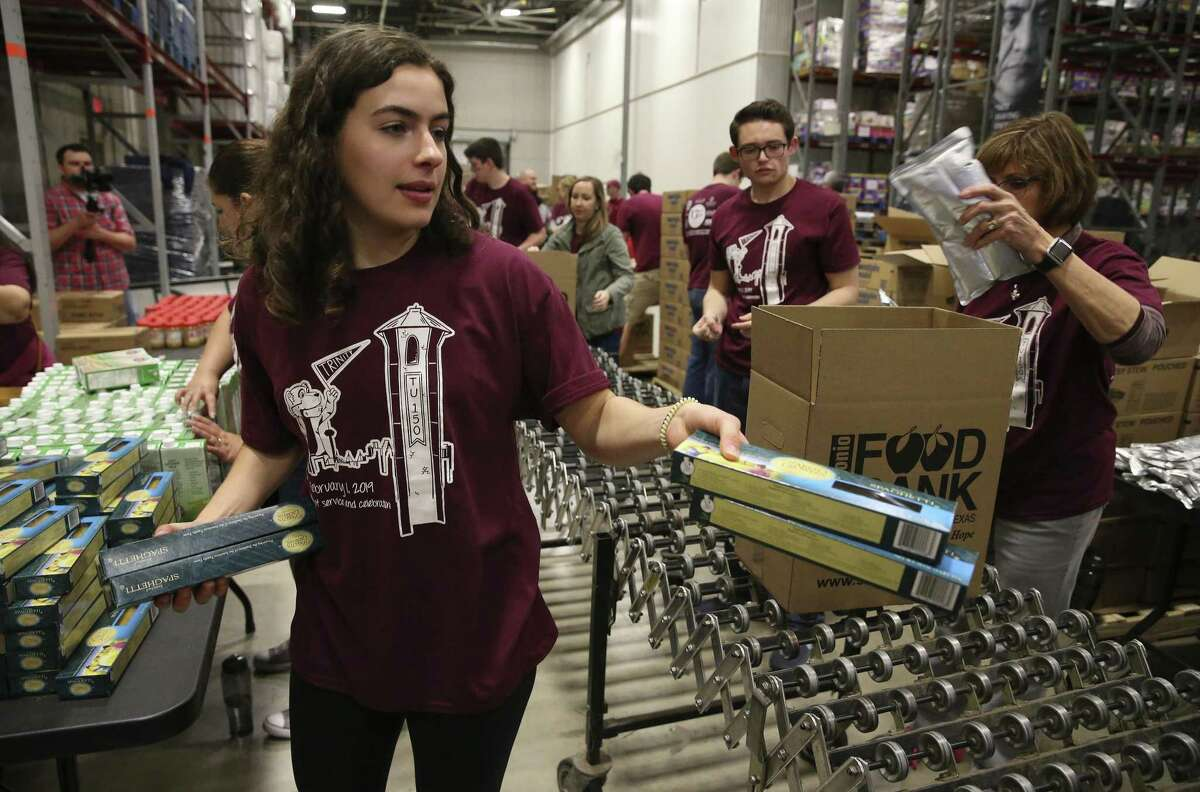 Trinity student Angela Campbell distributes pasta for others to pack in boxes at the San Antonio Food Bank on Friday, Feb. 1, 2019. Trinity University kicked off a year-long celebration of its 150th anniversary with an afternoon of city-wide community service projects. Students, alumni and employees went to the San Antonio Food Bank to volunteer their time packing boxes of food for seniors. About 150 people from Trinity turned out about 2,100 boxes of food containing juice, cereal, pasta, canned fruit, canned vegetables, protein, dry milk and peanut butter. The effort can usually take several days but with the turnout on Friday, the Trinity group had that quantity done in about two hours. (Kin Man Hui/San Antonio Express-News)