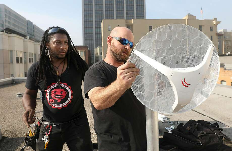 Monkeybrains technicians Isaiah Tweed (left) and Ari Schutz (right) place a wireless internet receiver on the roof of the Larkin Street Youth Services building on Tuesday, Nov. 20, 2018, in San Francisco, Calif. Photo: Liz Hafalia / The Chronicle