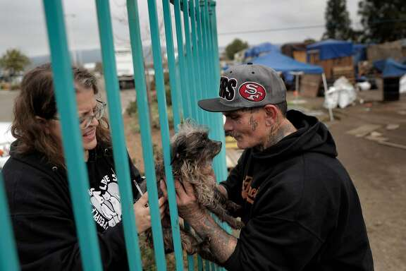 Jessica Lefebvre asks Kevin Alpiche to hold Sookie so she an apply flea medication through the fence from the Home Depot Parking lot to a homeless camp in Oakland, Calif., on Tuesday, January 29, 2019.  Jill Posner of Paw Fund, and Jessica Lefebvre of PALS East Bay are doing what they can to provide healthcare for the pets of the homeless and low income residents of the East Bay, through on site outreach and monthly clinics to help the less fortunate keep their pets healthy.