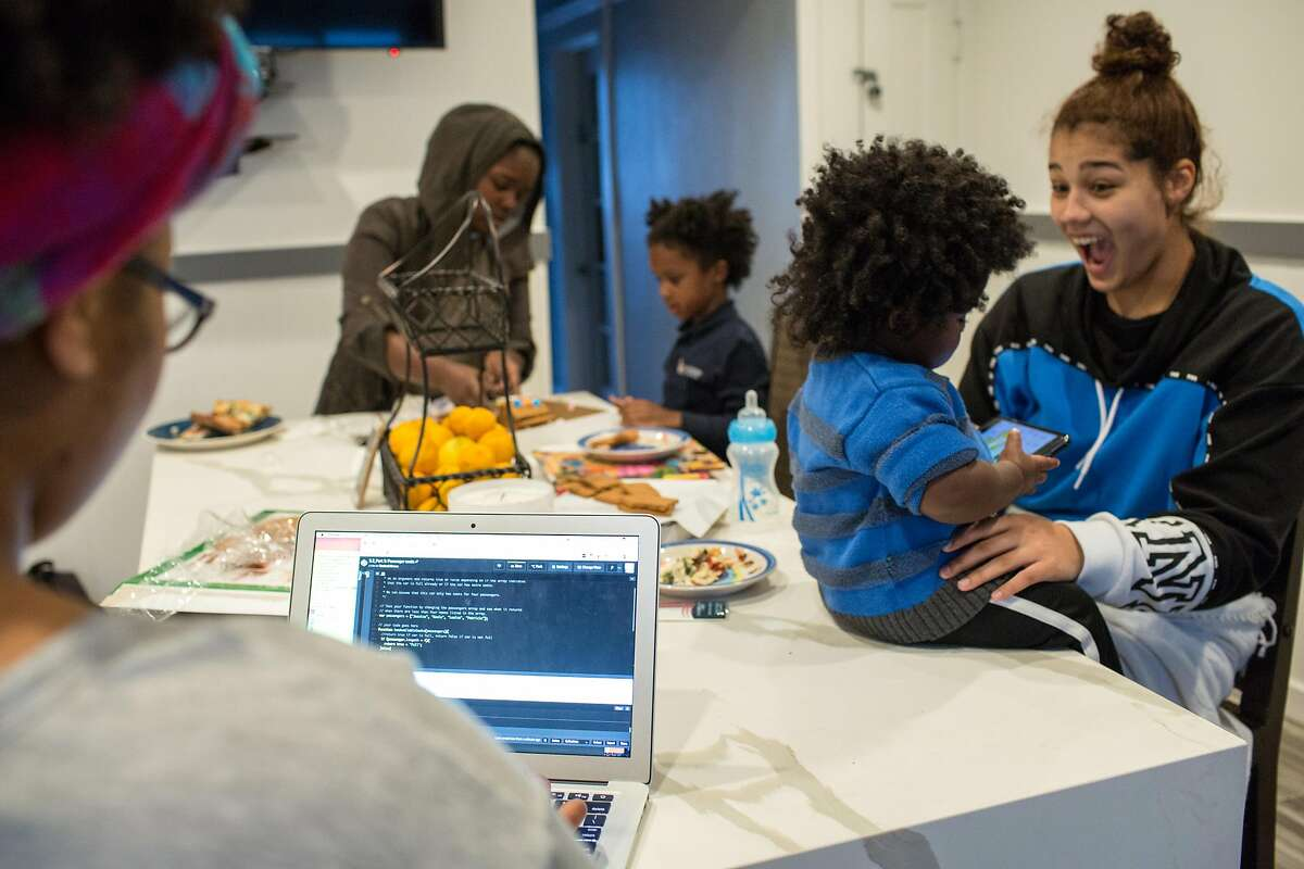 Daaimah Tibrey works on a computer to advance her coding assignment while her two kids, Jahdai and Malaika play with her sisters and decorate gingerbread cookies. Thursday, December 20, 2018 in San Francisco, Calif.