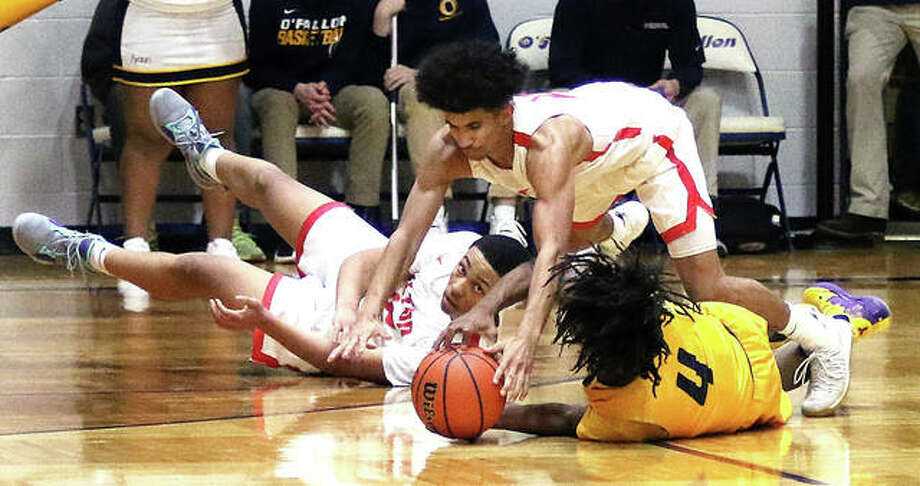 Alton's Andrew Jones (top) goes over Springfield Southeast's Terrion Murdix (4) for a loose ball while the Redbirds' Josh Rivers watches the play Friday night at the Bank of O'Fallon Shootout at Panther Dome in O'Fallon. Photo: Greg Shashack | The Telegraph