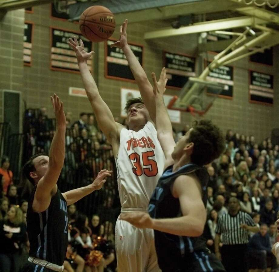 Ridgefield's Matt DeLuca grabs a rebound during Friday's game against Wilton. Photo: Scott Mullin / For Hearst Connecticut Media / Stamford Advocate Freelance