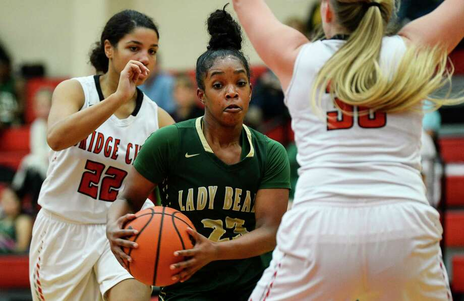LCM's Zaria Johnson works her way around Bridge City's Madison Fischer during the first half of the game at Bridge City on Friday.