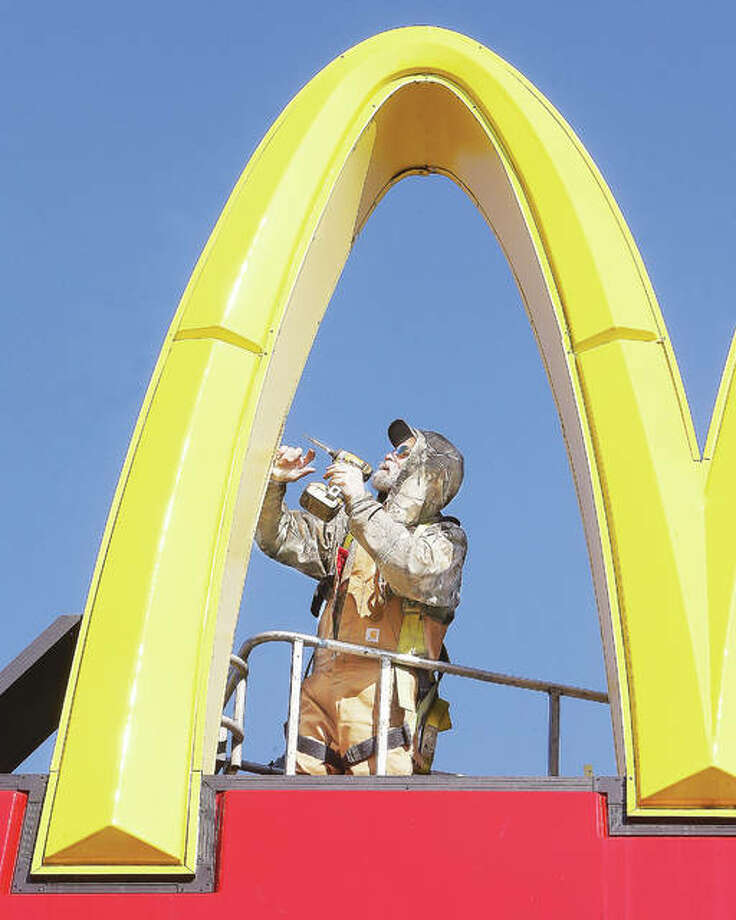 An employee of Piros Signs Inc. in Barnhart, Missouri, puts the golden arches of the downtown Alton McDonald's back together Friday after converting the lights inside to energy efficient LED fixtures. The extreme cold and high winds were making work a little slow this week, but the crew seemed to be making up for lost time with a seemingly balmy high temperature around 40 degrees. Sunday, the mercury is expected to hit a whopping 65 degrees before cooling down again next week. Photo: John Badman | The Telegraph
