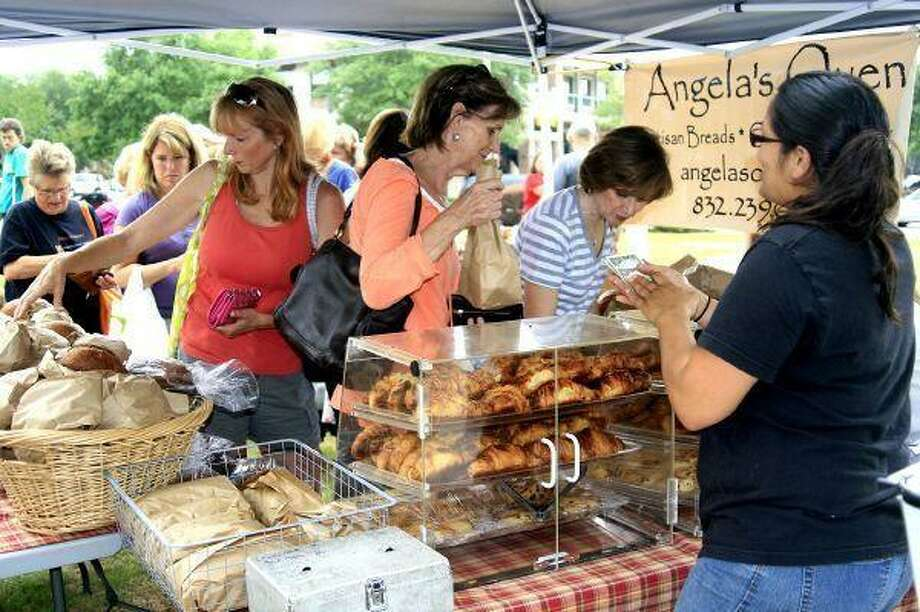 As soon as the booth opened for Angela's Oven at the Kingwood Farmer's Market a group of customers made sure to get their fresh baked breads and pastries before they were out May 13. Photo: JENNIFER SUMMER / The Observer / The Observer