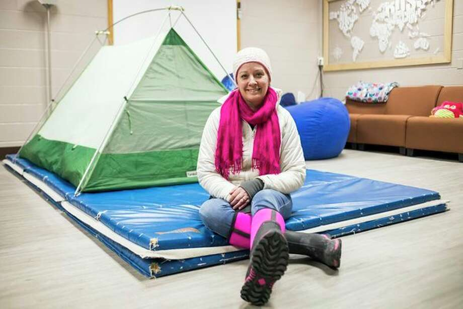 Tara Berger poses for a portrait Friday in front of the tent she and her boyfriend slept in the night before at West Midland Family Center. (Katy Kildee/kkildee@mdn.net)