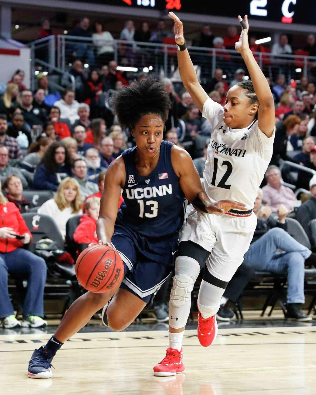 UConn's Christyn Williams (13) drives against Cincinnati's Antoinette Miller in the first half of a game last season in Cincinnati.