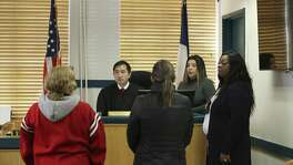 People accused of low-level misdemeanors appear before Travis County Justice of the Peace Precinct 5 Judge Nicholas Chu in Austin on Jan. 24, 2019. Police did not arrest them. Instead, under a cite and release program, they had been given a citation and told to appear in court within a month. With Chu are Court Clerk Maria Cristina Berrios, second from right, and Deputy Constable Kasben Harris, right. Berrios was interpreting for two Spanish-speaking defendants.