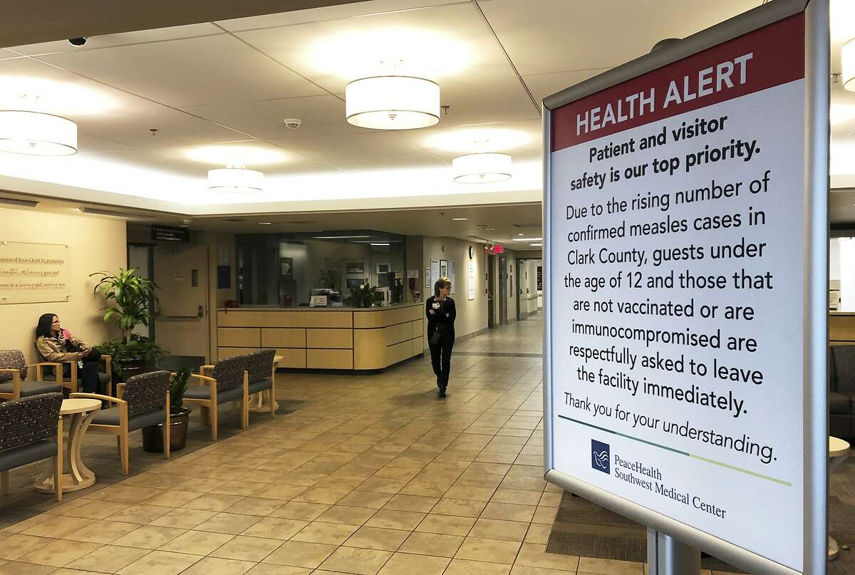A sign prohibiting all children under 12 and unvaccinated adults stands at the entrance to PeaceHealth Southwest Medical Center in Vancouver, Wash on Jan. 25, 2019. A measles outbreak that has sickened more than 40 people in the Pacific Northwest has prompted a call to eliminate a
