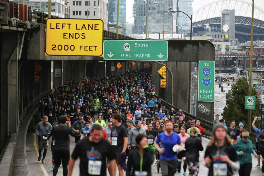 Twenty-nine thousand people participate in the Tunnel to Viaduct 8k, which allowed runners and walkers to travel south through the new SR 99 tunnel and north over the lower deck of the Alaskan Way Viaduct, Saturday, Feb. 2, 2019. Many runners stopped to take photos along the route, capturing what would be their last chance to walk along the viaduct before it is demolished later this month. The 8K is part of a weekend-long celebration marking the opening of the new tunnel, which 100,000 people were expected to attend. (Genna Martin, SeattlePI) Photo: GENNA MARTIN, Seattlepi.com / SeattlePI