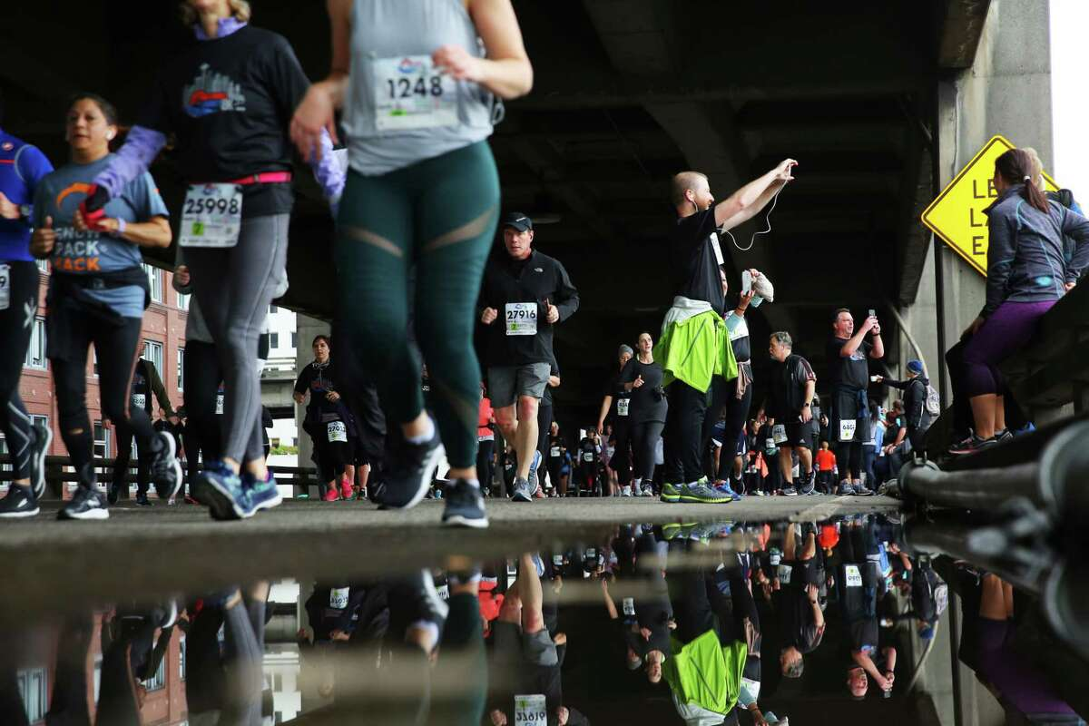 Twenty-nine thousand people participate in the Tunnel to Viaduct 8k, which allowed runners and walkers to travel south through the new SR 99 tunnel and north over the lower deck of the Alaskan Way Viaduct, Saturday, Feb. 2, 2019. Many runners stopped to take photos along the route, capturing what would be their last chance to walk along the viaduct before it is demolished later this month. The 8K is part of a weekend-long celebration marking the opening of the new tunnel, which 100,000 people were expected to attend. (Genna Martin, SeattlePI)