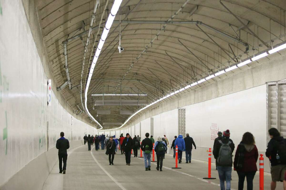 People walk through the new SR 99 tunnel after an official ribbon cutting ceremony to celebrate its opening, Saturday, Jan. 2, 2019. As many as 100,000 people are expected to attend the weekend-long celebration to say goodbye to the Alaskan Way Viaduct and hello to the new tunnel. (Genna Martin, SeattlePI)