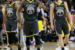 Golden State Warriors guard Andre Iguodala (9), forward Draymond Green (23) and guard Klay Thompson (11) during a timeout in the first half of an NBA game against the Los Angeles Lakers at Oracle Arena on Saturday, Feb. 2, 2019, in Oakland, Calif.