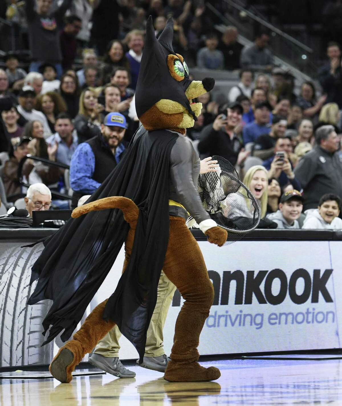 The Spurs Coyote and an assistant walk off the court with a bat that they caught during NBA action in the AT&T Center on Saturday, Feb. 2, 2019. The flying mammals have taken up residence in the arena.