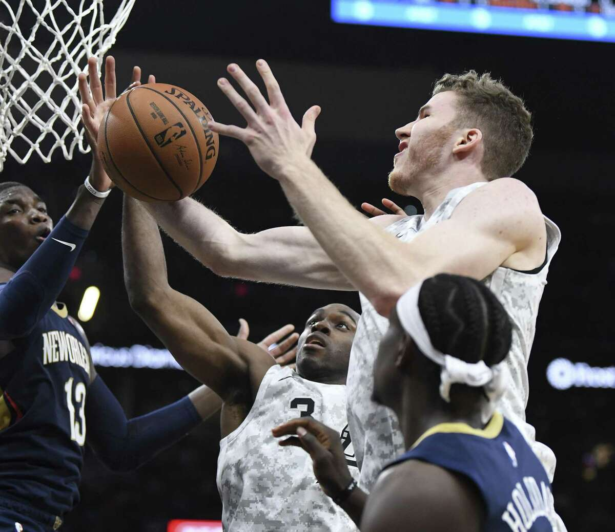 Jakob Poeltl of the San Antonio Spurs comes down with a rebound as teammate Quincy Poindexter (3) and Cheick Diallo (13) and Jrue Holiday (11) of the New Orleans Saints reach for it during NBA action in the AT&T Center on Saturday, Feb. 2, 2019.