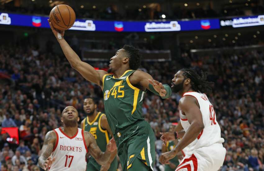 Utah Jazz guard Donovan Mitchell (45) lays the ball up as Houston Rockets' PJ Tucker (17) and Nene Hilario (42) defend during the second half of an NBA basketball game Saturday, Feb. 2, 2019, in Salt Lake City. (AP Photo/Rick Bowmer)