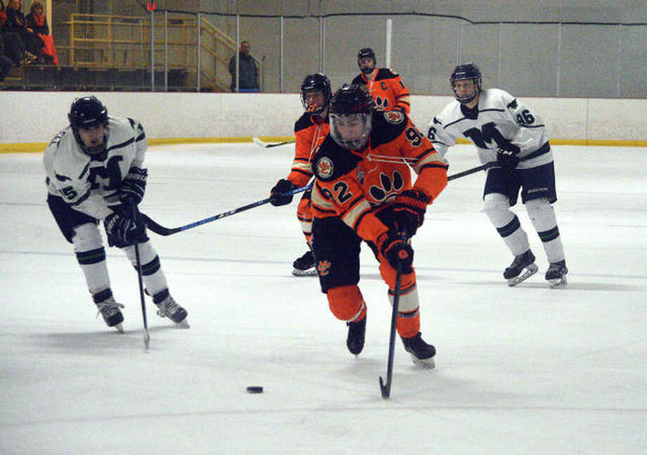 Edwardsville senior Matt Kocarnik, middle, carries the puck during the first period of Saturday's game against Marquette at the Brentwood Ice Rink. Photo: Scott Marion/Intelligencer