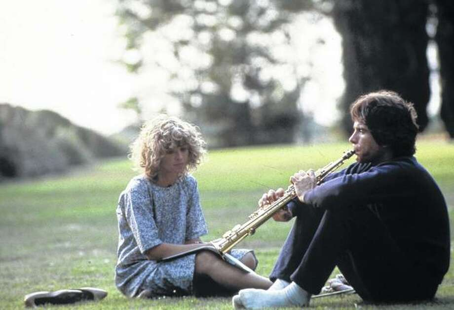 """Julie Christie sits in the grass with Warren Beatty in a scene from the 1978 film """"Heaven Can Wait"""". Photo: Paramount 