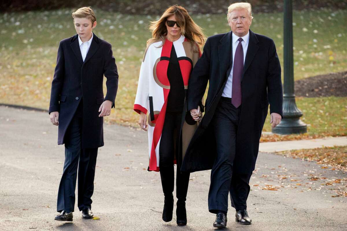 In this Nov. 20, 2018, file photo President Donald Trump accompanied by first lady Melania Trump, and their son Barron, left, walks towards Marine One on the South Lawn of the White House in Washington.