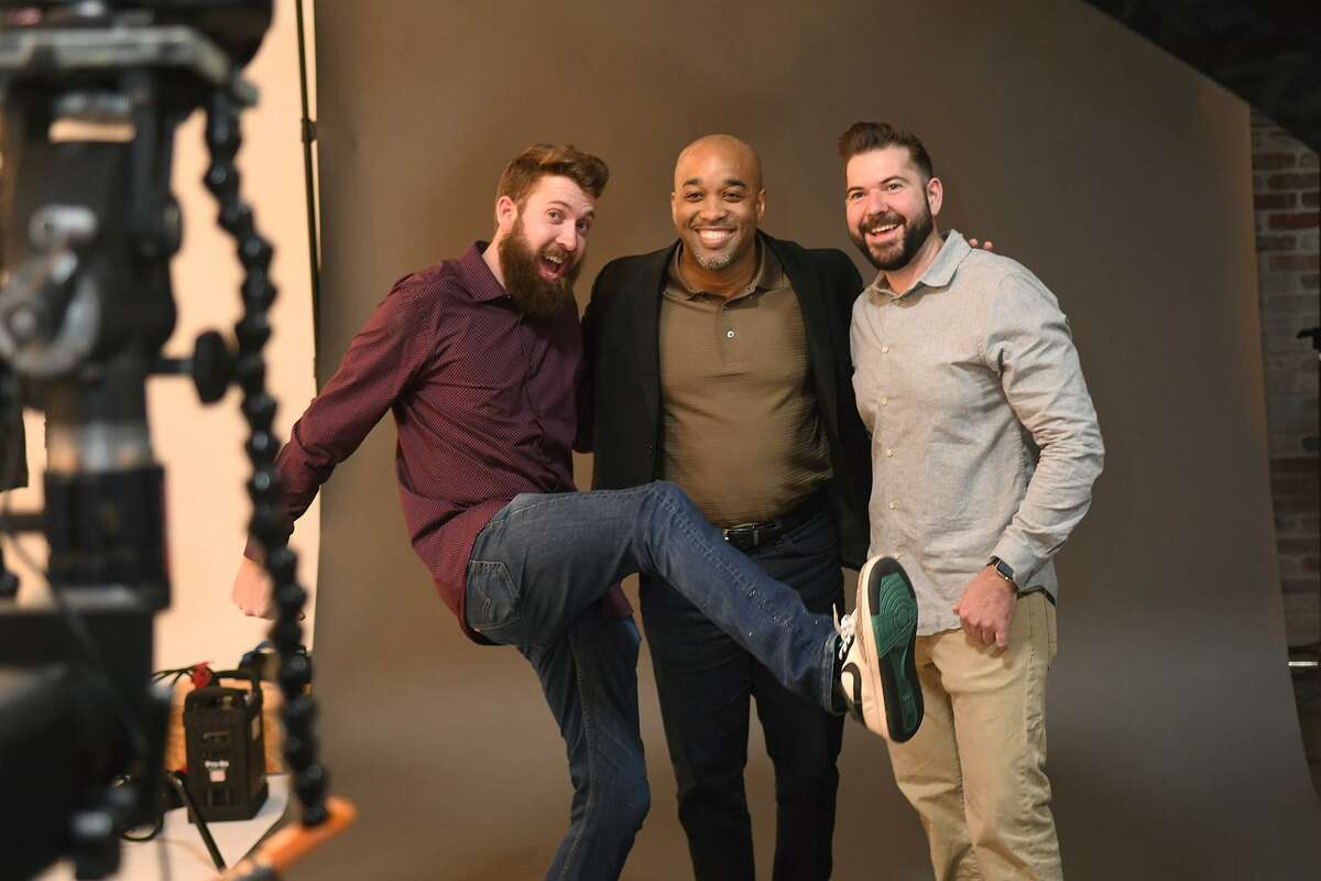Chris Wohrer, left, and his brother Jeff, co-owners of Moffett Productions, share a photo in the studio/sound stage of their business with Clarence Estes of You Squared Media during their grand opening in Tomball on Feb. 1, 2019.