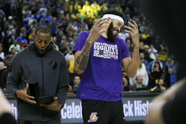 Golden State Warriors guard Andre Iguodala (9) hid the championship ring from former Warriors and now Los Angeles Lakers center JaVale McGee (7) before NBA game at Oracle Arena on Saturday, Feb. 2, 2019, in Oakland, Calif.
