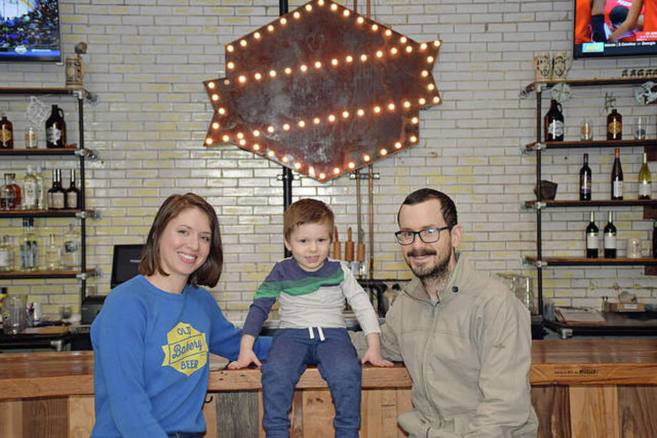 Lauren Pattan, James Rogalsky, and their son Murray at the repurposed, 100-year-old bar inside the Old Bakery Beer Company. Photo: David Blanchette | For The Telegraph