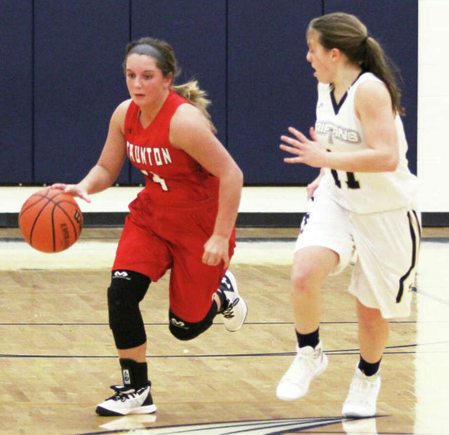 Staunton's Savannah Bruhn (left) brings the ball upcourt against pressure from Father McGivney's Macy Hoppes in a Dec. 17 game in Glen Carbon. On Saturday, Bruhn scored 17 points to lead the Bulldogs past Pawnee for a school-record 22nd victory. Photo: Greg Shashack / The Telegraph