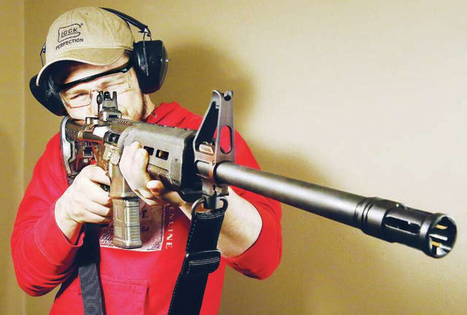 A card-holding gun range user takes aim with a Ruger AR-15/M4, which would be among the many weapons banned from sale in Illinois under proposed SB107. The bill, as currently written, essentially bans all rifles with detachable magazines, including the Ruger 10/22 rifle used by many youths to learn their shooting and hunting skills. The Ruger 10/22 is the most popular .22LR chambered rifle in the United States. Many of the restrictions in SB0107 would be more restrictive than laws passed in the state of California, which is widely considered to be one of the most restrictive states in the country on gun owners. Photo: John Badman | Hearst Illinois