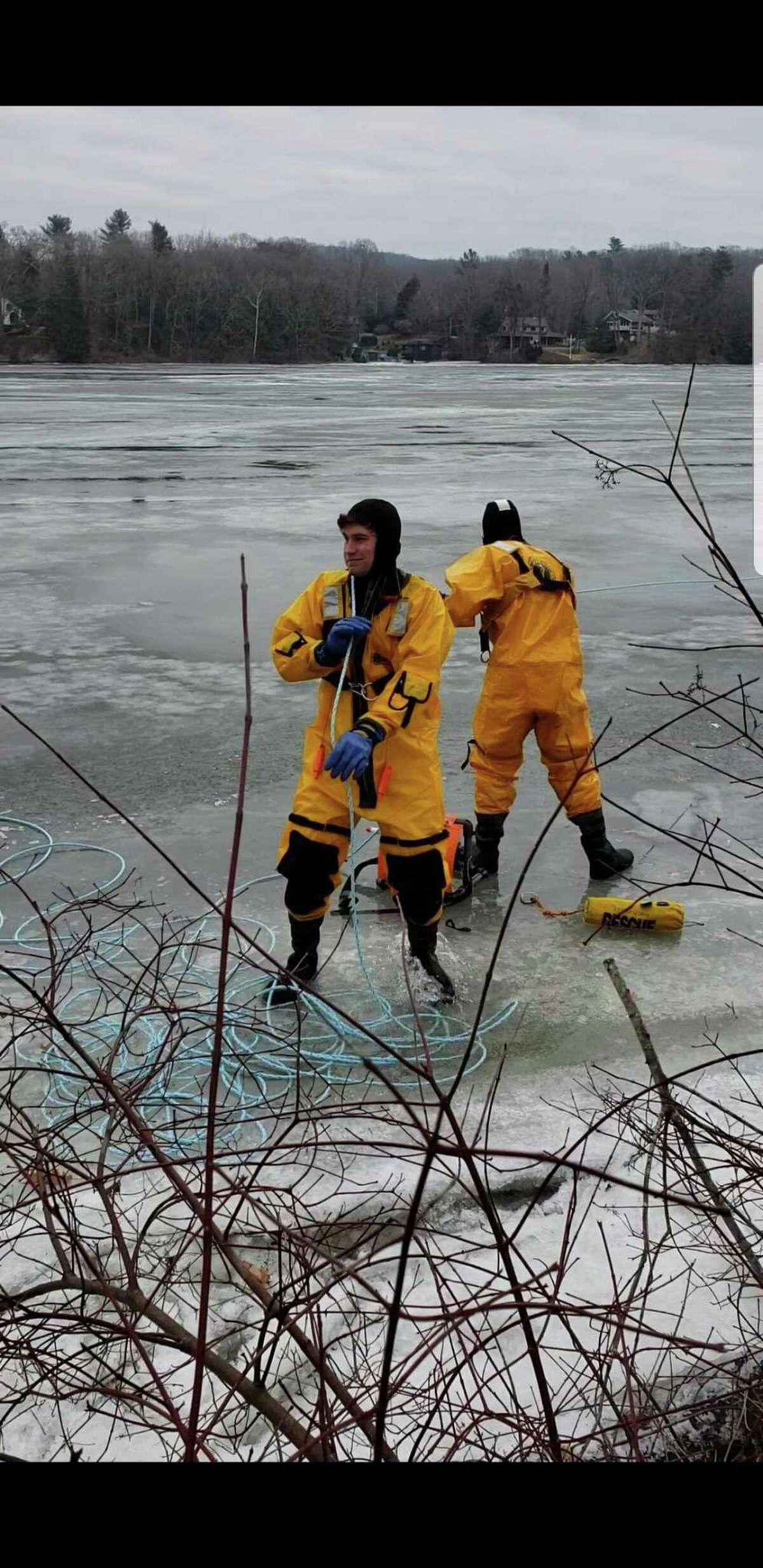 Firefighters Brock Butkovsky (left) and Chris Moquin (right) help rescue a deer that became stranded on the ice on Lake Zoar on Feb. 3, 2019.