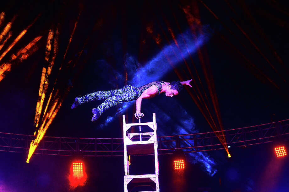 A performer balances atop a tower of chairs amid the colorful lights during the Garden Brothers Circus' opening show at Ford Park Arena Friday. Families can enjoy the acrobats, clowns and other acts Saturday, with performances taking place at 1:30, 4:30 and 7:30 p.m. Photo taken Friday, February1, 2019 Photo by Kim Brent/The Enterprise Photo: Kim Brent/The Enterprise