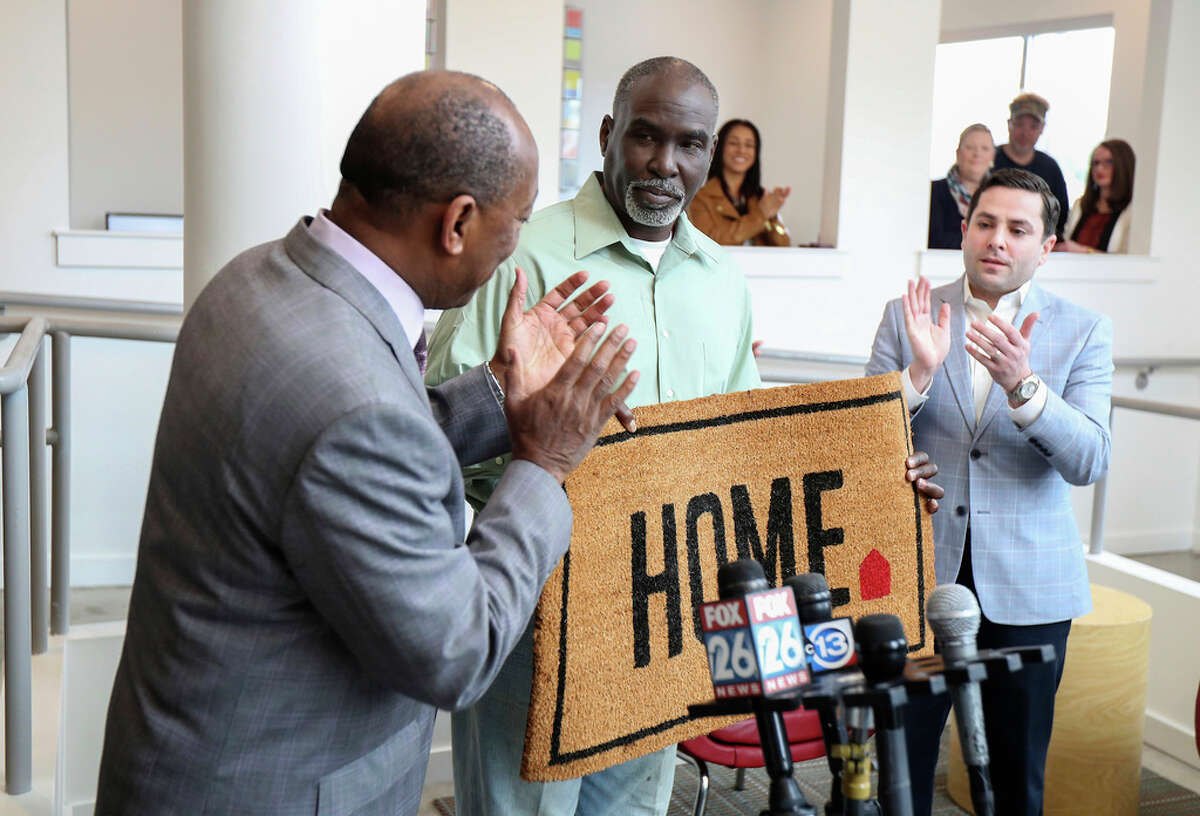 In this Friday, Feb. 1, 2019 photo, Mayor Sylvester Turner, left, and Special Assistant to the Mayor for Homeless Initiatives Marc Eichenbaum, right, welcome Joseph to his new home through The Way Home program in Houston. Joseph was homeless and lived in the homeless encampment on Wheeler in Midtown before moving into his new home at New Hope Housing. (Steve Gonzales/Houston Chronicle via AP)