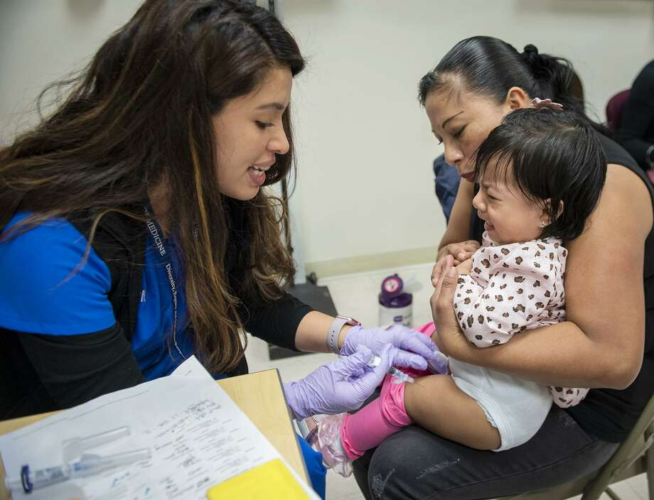 Crystel, 15 months, cries as she gets a vaccination from nurse Cinthya Chumpitaz during a Yale Clinic for Hispanic Children visit. Holding Crystel is her mom, Audelina. Photo: Melanie Stengel / Contributed Photo