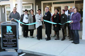 Staff members from the city of Edwardsville, the Edwardsville/Glen Carbon Chamber of Commerce and The Reserve celebrate the student housing complex's grand opening Friday afternoon with a ribbon cutting. The Reserve will house 486 students this August.