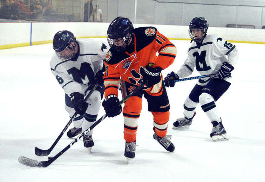 Edwardsville junior Sam Gibbons, middle, battles for the puck with two Marquette players during the third period of Saturday's game against Marquette at the Brentwood Ice Rink. Photo: Scott Marion | For The Telegraph