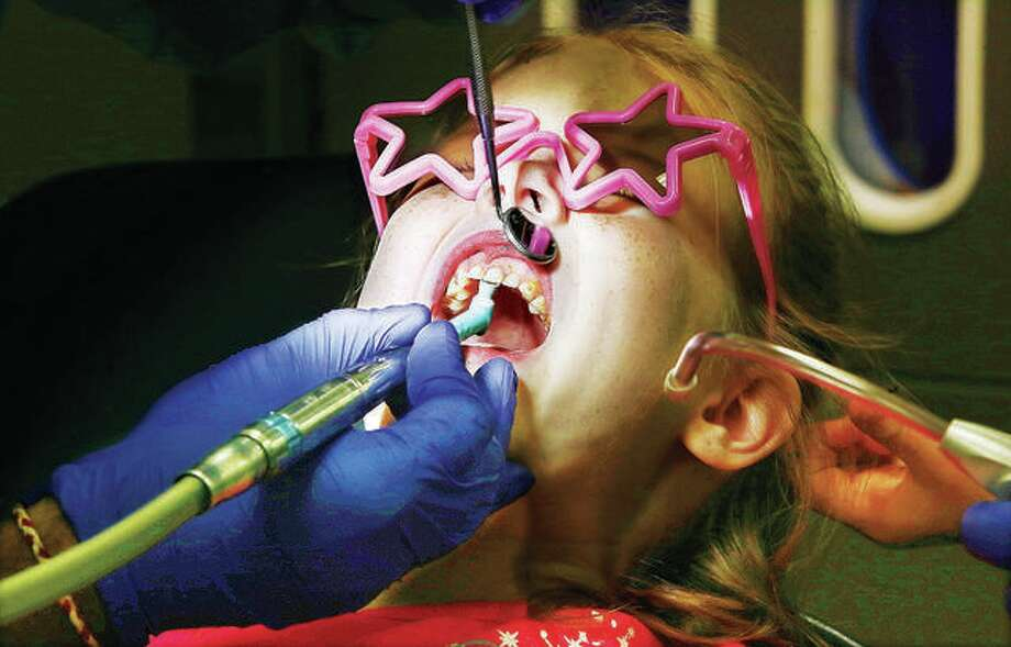 6-year-old Kaylynn may have looked uncomfortable, but she was actually giggling most of the time as a cleaning and sealant were applied to her teeth and tickling her mouth at the SIU School of Dental Medicine clinic in Alton last year. Photo: John Badman | Hearst Illinois File Photo