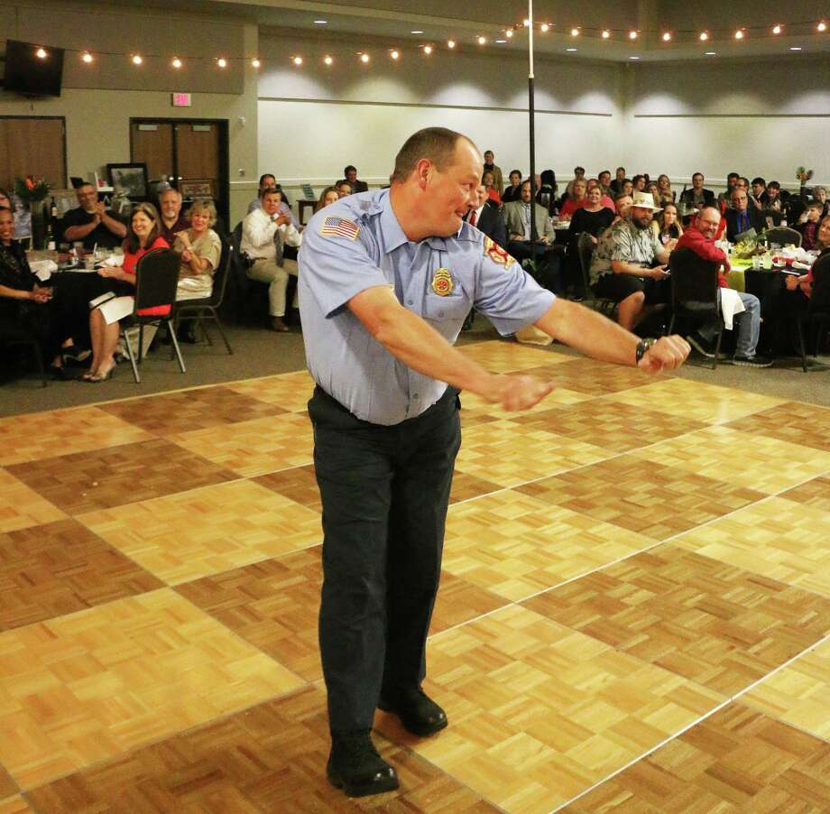 "Fireman Josh Alley danced his way to the podium with his signature dance, ""The Joshua,"" to accept his award as Fire Fighter of the Year at the Dayton Chamber of Commerce last Saturday night. Photo: David Taylor / Staff Photo"