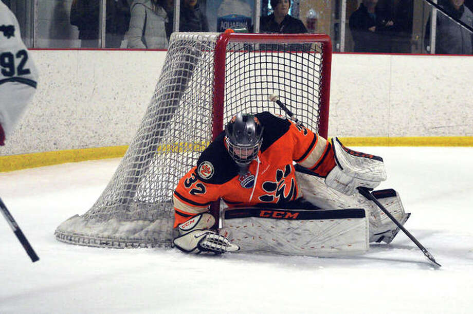 Edwardsville goalie Mason Young covers up the puck during the second period of Saturday's game against Marquette at the Brentwood Ice Rink. Photo: Scott Marion/Intelligencer