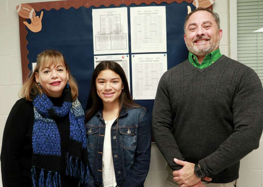 Cigarroa High School junior Ashly Torres is congratulated by Cigarroa High School Principal Laura Flores and LISD Child Nutrition Program Director Robert Cuellar for being named a Texas health ambassador for the Texas Department of Agriculture. Photo: LISD /Courtesy Photo