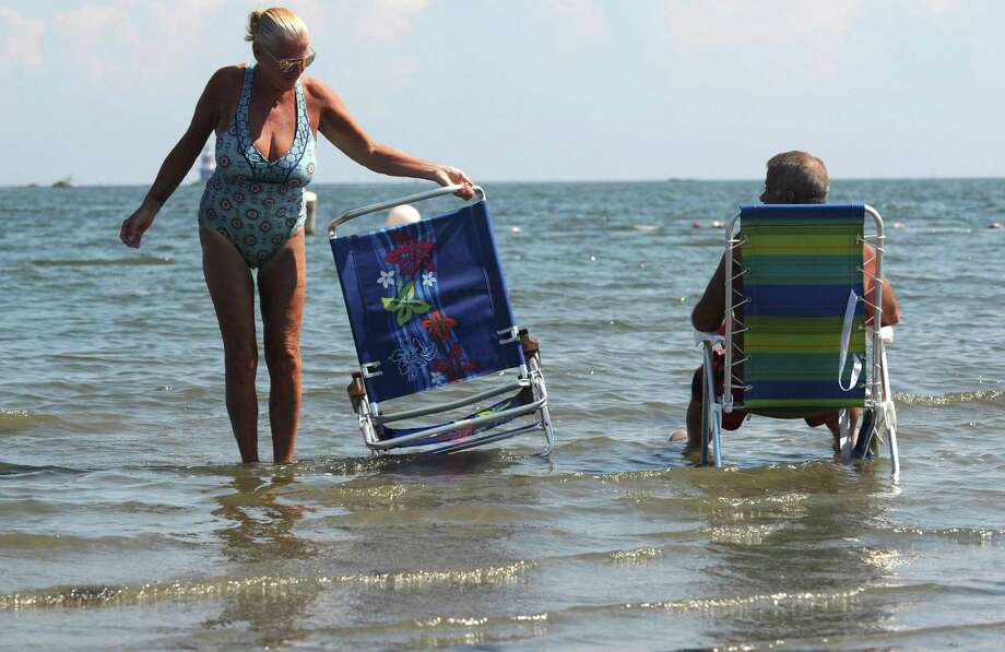 Norwalk resident Andrea Wilson adjusts her chair as she and Jerry Harris beat the heat by soaking in the waters at Calf Pasture Beach Wednesday, September 5, 2018, in Norwalk, Conn. Photo: Erik Trautmann / Hearst Connecticut Media / Norwalk Hour