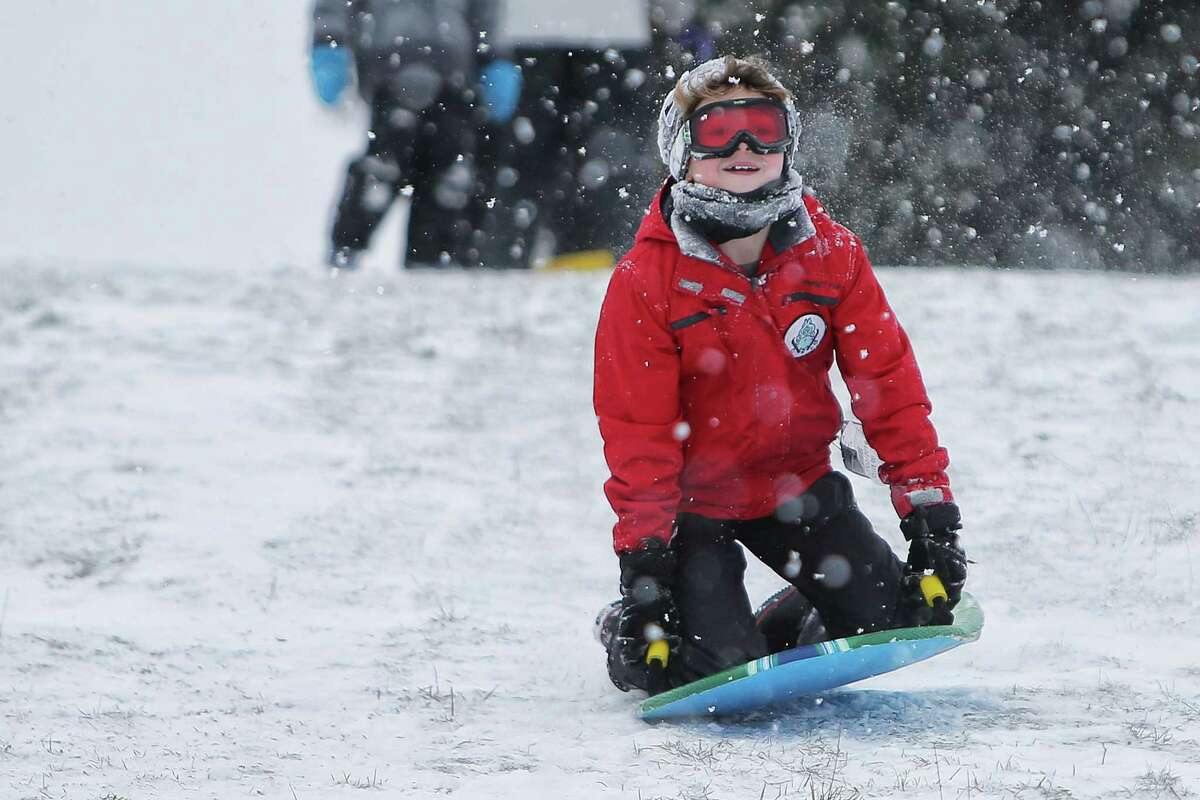FILE -- Kids and parents enjoy a snow day, sledding at Westcrest Park in White Center, Monday, Feb. 4, 2019. Seattle Public Schools were closed for the day due to several inches of snow that fell overnight and through the morning.