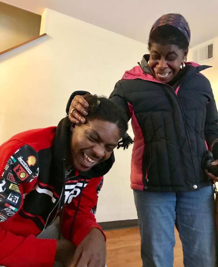 Ellazar Williams shares a playful moment with Alice Green, executive director of the Center for Law and Justice. Williams, shot by police in August and paralyzed as a result of the incident, is shown in his North Albany apartment on Jan. 27, 2019.