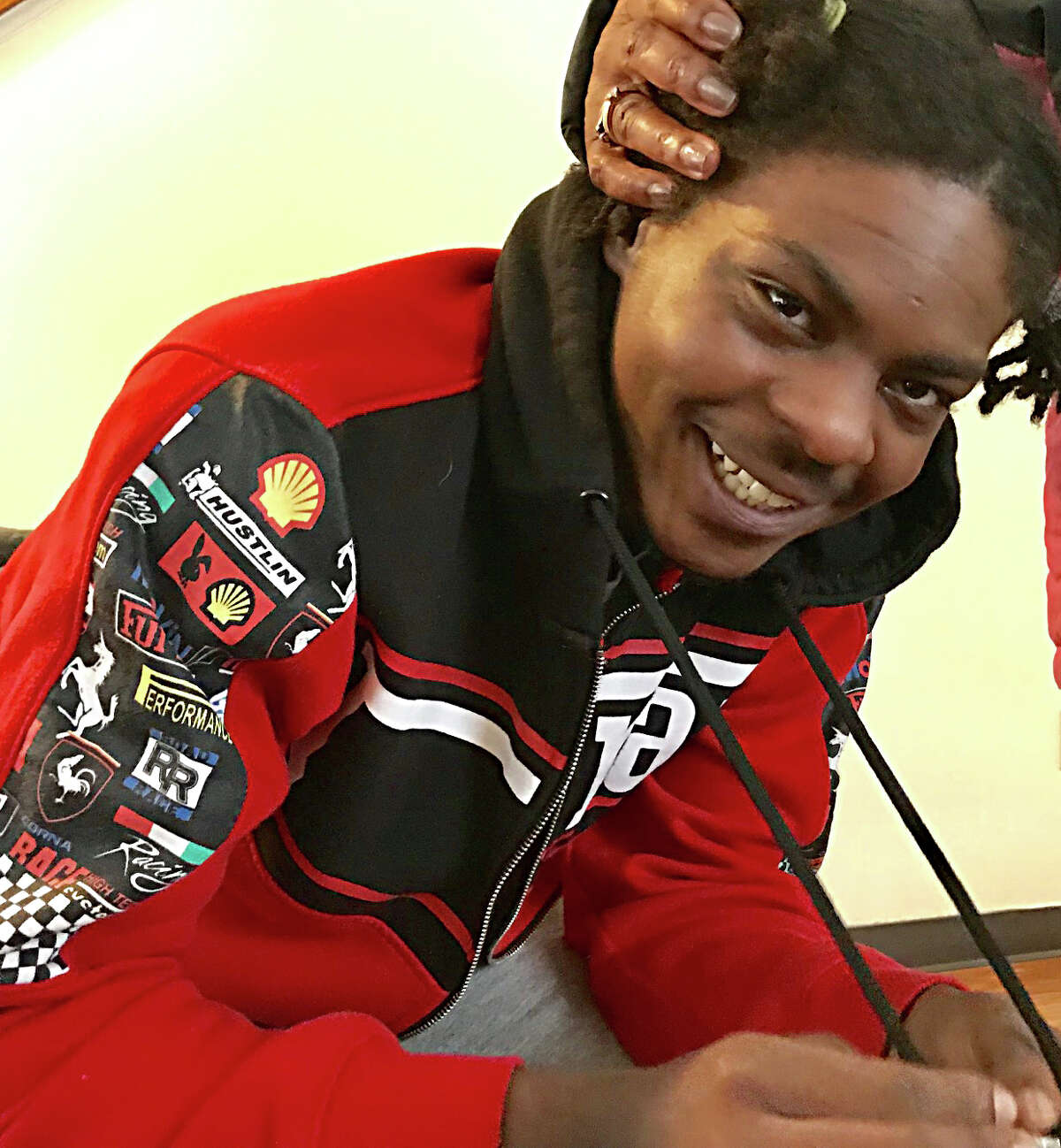 Ellazar Williams, shot by police in August and paralyzed as a result of the incident, smiles in his North Albany apartment after getting a pat on the head from Alice Green,executive director of the Center for Law and Justice, on Jan. 27, 2019. (Paul Grondahl/Times Union)