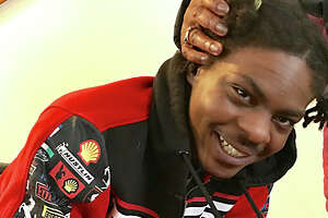 Ellazar Williams, shot by police in August and paralyzed as a result of the incident, smiles in his North Albany apartment after getting a pat on the head from Alice Green, executive director of the Center for Law and Justice, on Jan. 27, 2019.  (Paul Grondahl/Times Union)