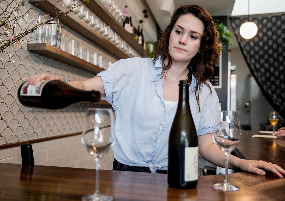 Owner Olivia Maki pours a glass of Eve's Cidery's Darling Creek dry cider behind the bar of Redfield Cider Bar in Oakland, Calif. Saturday, Feb. 2, 2019.