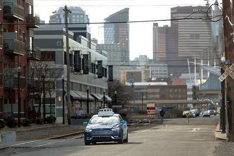 In this Dec. 18, 2018, photo one of the test vehicles from Argo AI, Ford's autonomous vehicle unit, navigates through the strip district near the company offices in Pittsburgh. Even the most optimistic experts say it will be 10 years before self-driving vehicles are everywhere, but others believe it will take decades. The biggest reasons are camera and laser sensors that can't see through heavy snow or figure out where to go if lane lines are covered. (AP Photo/Keith Srakocic)
