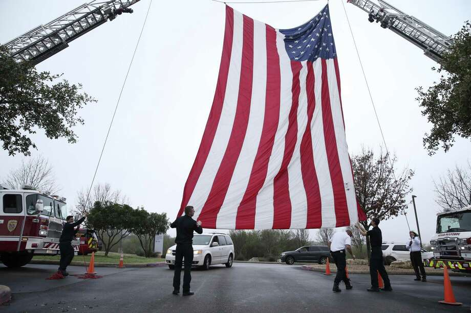 San Antonio Fire Department personnel raise a flag before the procession carrying Bexar County Sheriff's K-9 Deputy Chucky arrives for funeral services at Community Bible Church, Monday, February 4, 2019. Chucky died in the line of duty on January 26. Photo: Jerry Lara / Staff Photographer / © 2019 San Antonio Express-News