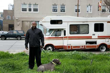 Ernest Owens stands with his dog Blue as they pose for a portrait near the RV that he lives in with his wife Lisa Photo: Yalonda M. James / The Chronicle